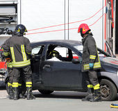 Firefighters in action during the car accident Stock Image