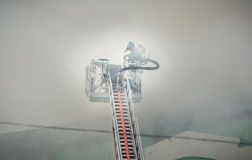 Firefighters in action fighting, extinguishing fire, in smoke. Royalty Free Stock Images