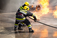 Firefighters in action. Fire department training. Firefighters attack a propane fire during a training exercise stock image