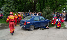 Firefighters in action. Public simulation of car accident. Firefighters helping a victim incarcerated under the car Stock Images