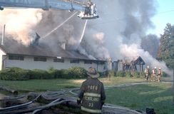 Firefighters in a aerial platform fire truck fight a 3 alarm fire stock image