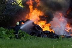 Firefighters battle. With burning tires Royalty Free Stock Image