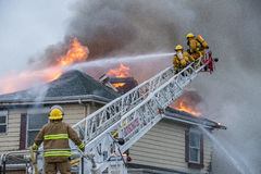Firefighters battle blazing house fire Stock Images