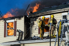 Firefighters battle blazing house fire.  Royalty Free Stock Photography