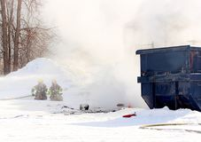 Firefighters battling dumpster fire on a cold winter day. Can be used for training video or cautionary tale of what not to put into construction bin Royalty Free Stock Photography