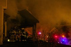 Firefighters Breaking Into a Burning House Royalty Free Stock Image