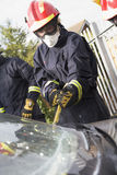 Firefighters breaking a car windscreen Stock Images