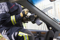 Firefighters breaking a car windscreen Royalty Free Stock Images