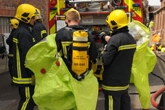 Firefighters in breathing apparatus don protective suits. Stock Images