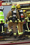 Firefighters in breathing apparatus with fire engine stock photo