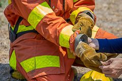 Firefighters buddy help to wearing fire protection gloves. Firefighters buddy help fireman to wearing fire protection gloves royalty free stock photos