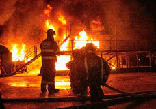 Firefighters in bunker gear facing white hot inferno with billowing smoke Stock Photography