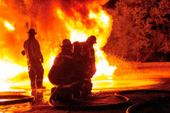 Firefighters in bunker gear facing white hot inferno Stock Photo