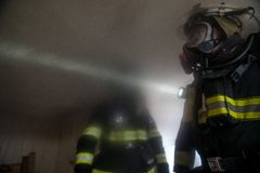 Firefighters In burning farm house Stock Photos