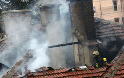 Firefighters burning house. Firefighters on a burning house roof royalty free stock photography