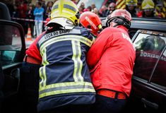 Firefighters car crash rescue scenery. Firefighters rescue team show to public how to remove from a car a wounded individual stacked inside Stock Images
