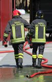 Firefighters carry the hydrant and hose pipes after put off the Royalty Free Stock Photography