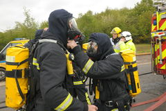 Firefighters check breathing apparatus. England. May 2012. Firefighters check their breathing apparatus at the scene of an accident stock images