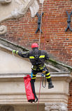 Firefighters climbing with ropes and climbing equipment on an ol. Brave firefighters climbing with ropes and climbing equipment stock images