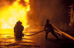 Firefighters controlling water hose Royalty Free Stock Photos