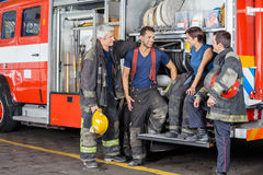 Firefighters Conversing By Firetruck Stock Photo