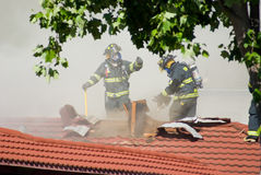 Firefighters Cutting Through Roof. Firefighters combating a house fire in a local neighborhood Royalty Free Stock Photography