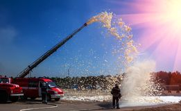 Firefighters demonstration of fire fighting equipment at sunset Royalty Free Stock Image