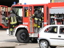Firefighters descend quickly from firetruck. Two Firefighters descend quickly from firetrucks after the road accident Stock Image