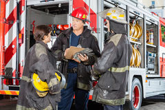 Firefighters Discussing Over Clipboard Against Royalty Free Stock Images