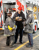Firefighters Discussing Over Clipboard At Fire. Full length of male and female firefighters discussing over clipboard against truck at fire station Royalty Free Stock Photos