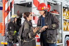 Firefighters Discussing Over Digital Tablet Stock Photos
