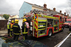 Firefighters and engine at house fire Royalty Free Stock Photography