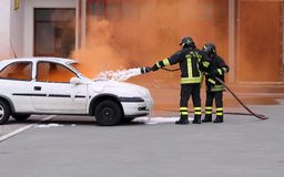 Firefighters during exercise to extinguish a fire in a car Royalty Free Stock Image