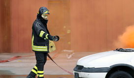 Firefighters during exercise to extinguish a fire in a car Stock Photography