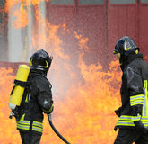 Firefighters during exercise to extinguish a fire in a car Stock Photos
