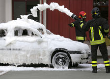 Firefighters during exercise to extinguish a fire in a car Stock Image