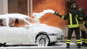 Firefighters during exercise to extinguish a fire in a car Stock Images
