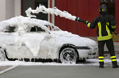 Firefighters during exercise to extinguish a fire in a car. Firemen during exercise to extinguish a fire in a car with foam Stock Images