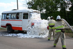 Firefighters  extinguish a burning bus. Firefighters in gas masks with foam extinguish a burning bus Stock Image