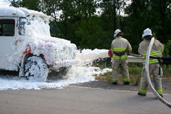 Firefighters extinguish a fire in a burning bus Royalty Free Stock Photo