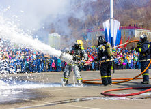 Firefighters extinguish the fire with foam in the smoke. Stock Image