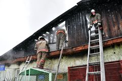 Firefighters extinguish a fire on the roof Stock Images