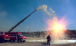 Firefighters extinguish the sun with foam. Royalty Free Stock Photos