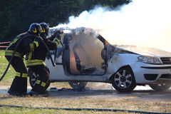 Firefighters extinguishing car on fire. Royalty Free Stock Photos