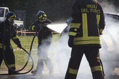 Firefighters extinguishing car on fire. Royalty Free Stock Photography