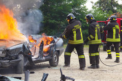 Firefighters extinguishing car on fire. Stock Photo