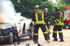 Firefighters extinguishing car on fire. Stock Photos