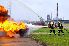 Firefighters extinguishing fire against the background of the re Stock Images