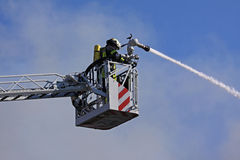 Firefighters fighting. Fire from bucket atop a fire truck stock photos