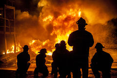 Firefighters fighting burning blaze Royalty Free Stock Images